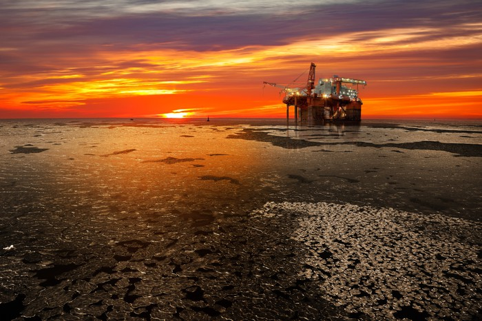 An offshore oil and rig platform at sunrise on a frozen sea.