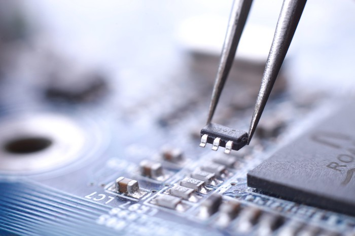 A microchip being placed on a motherboard with tweezers.