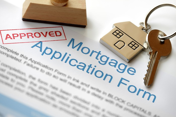 "A mortgage application stamped ""approved,"" with a stamper and a house key lying on top."