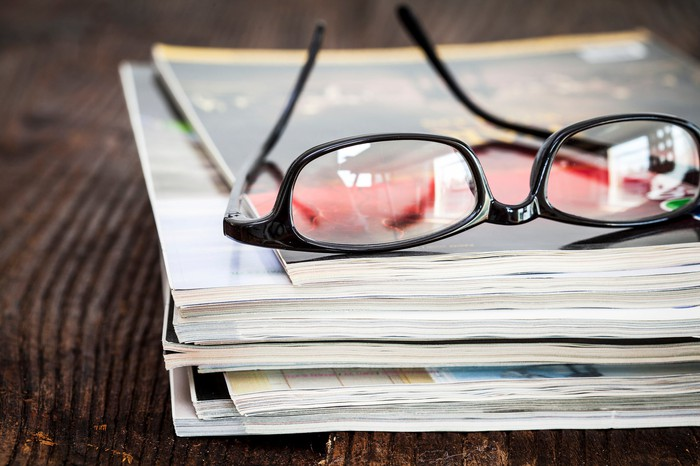 Eyeglasses on top of a stack of magazines