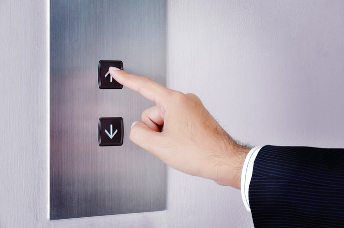 A businessman presses the up button in an elevator.