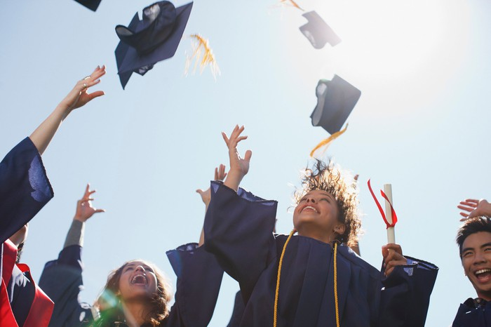 College graduates cheer as they throw their caps into the air.
