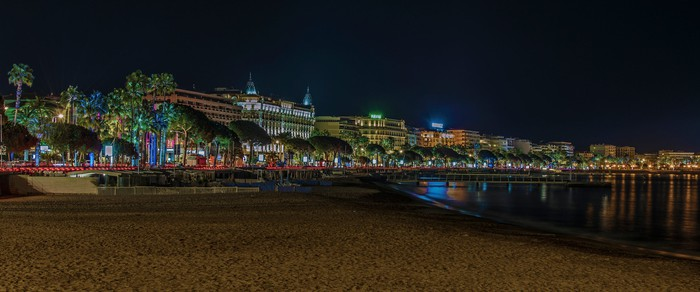 The illuminated city of Cannes, France, from the beach at night.