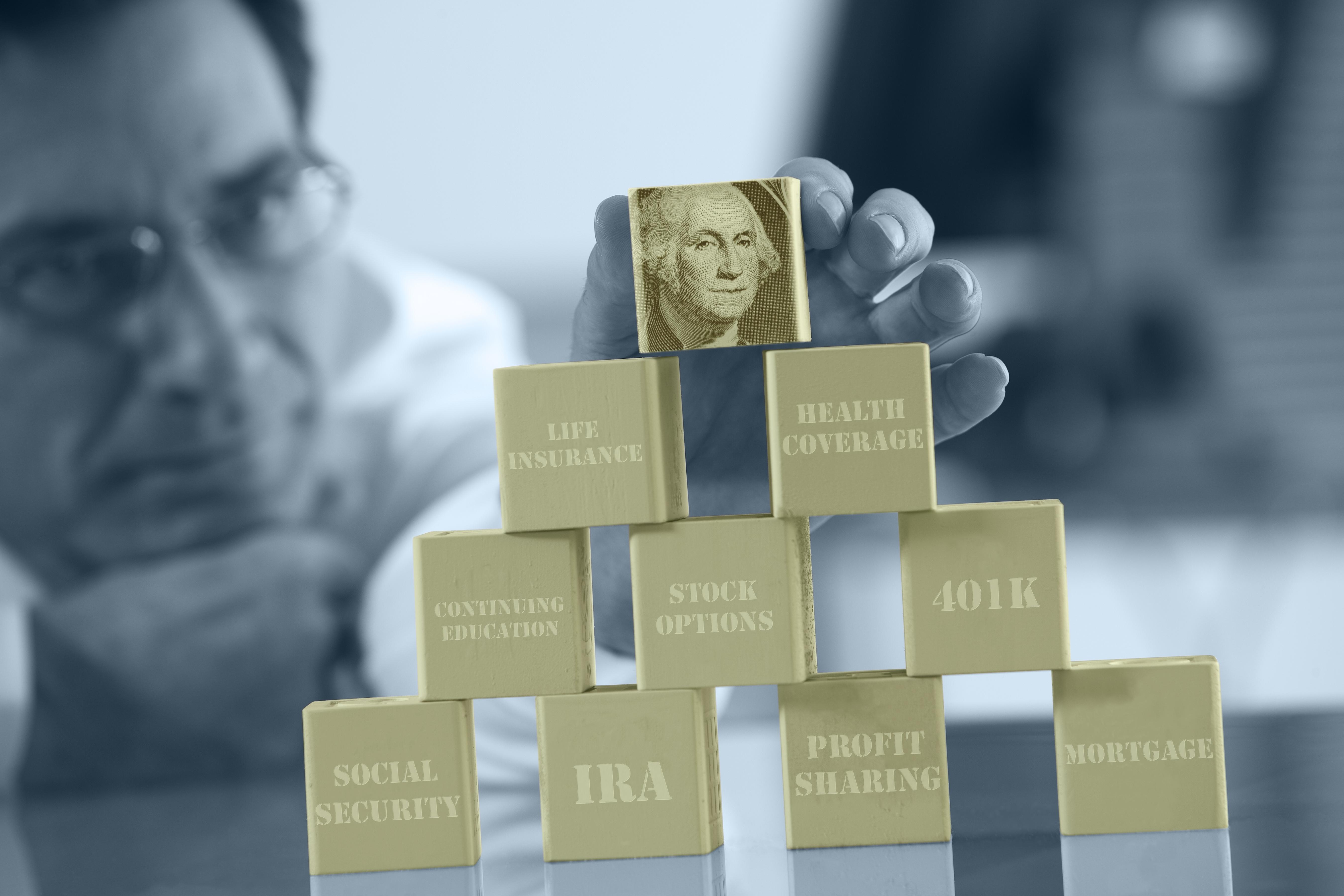 A man stacks gold-colored blocks that represent financial building blocks.