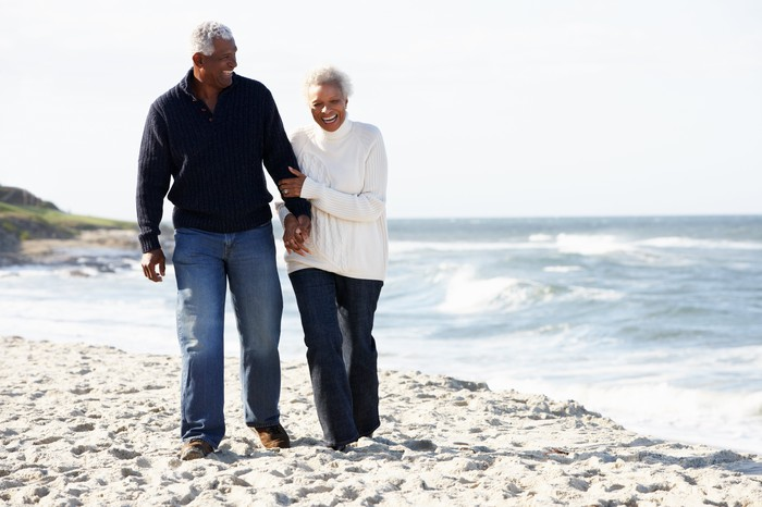 A senior couple walks on the beach, holding hands.