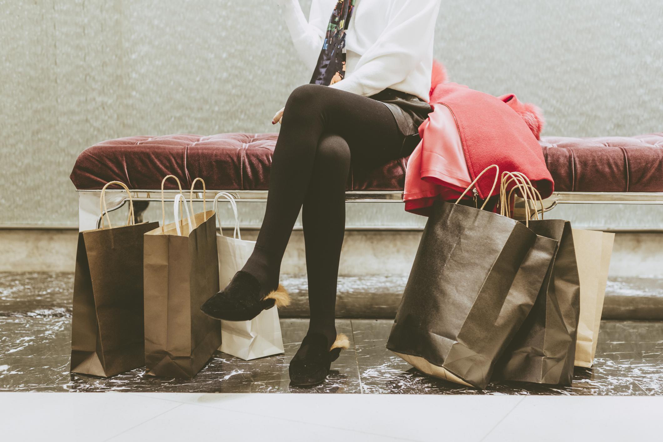 Shopping bags piled at a woman's feet.