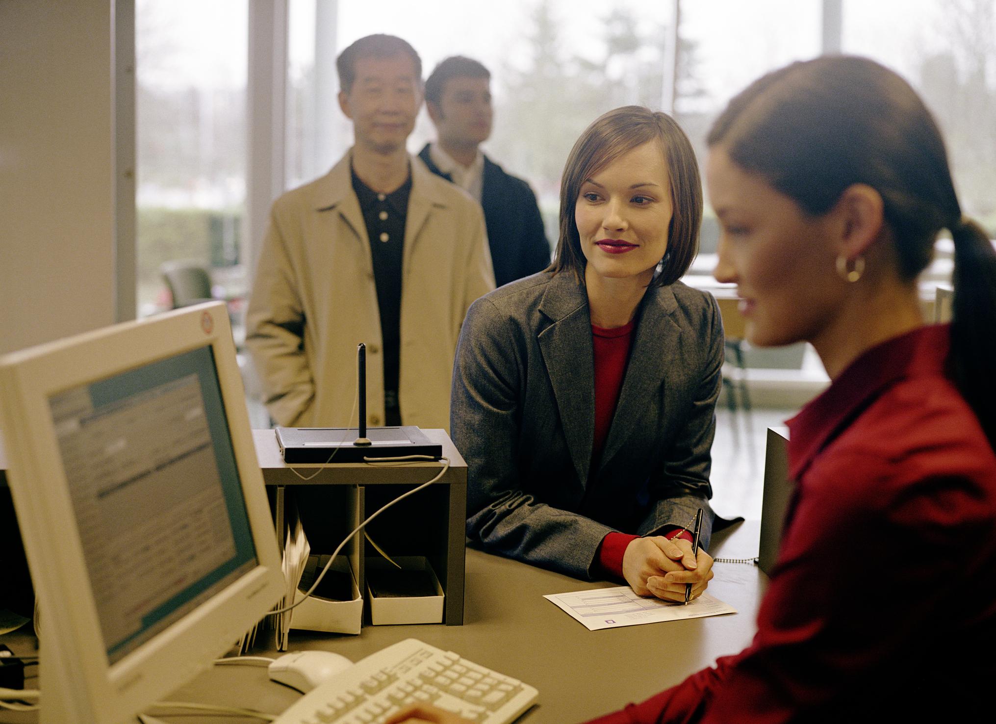A bank teller helping customers.