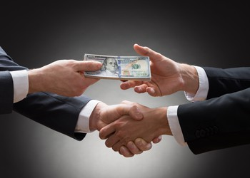 businessmen shaking hands and exchanging money