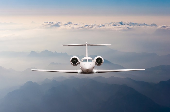Private jet flying above the clouds.