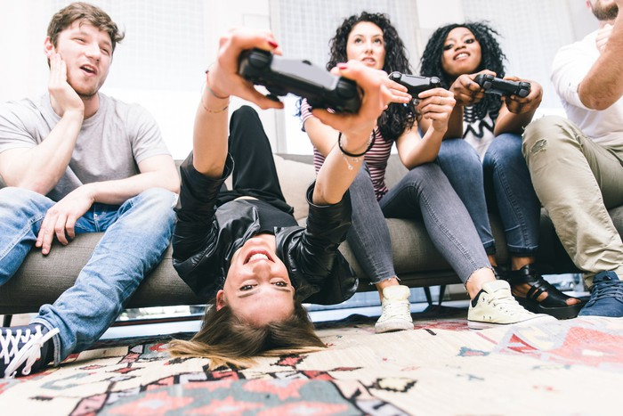 Group of friends smiling while holding controllers, sitting on a couch, playing video games.