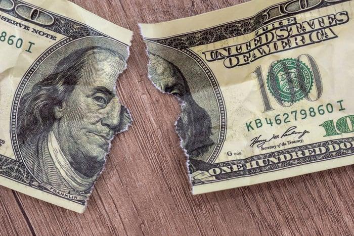 100 dollar bill torn in half.