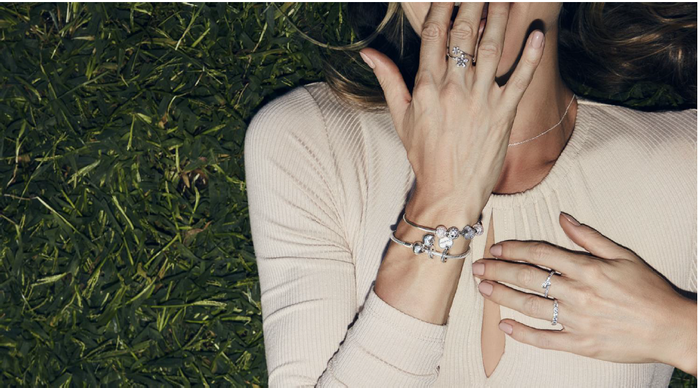 Woman from neck down wearing Pandora rings and bracelets
