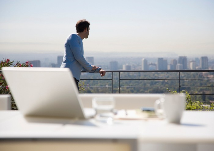 Man contemplates decision on a deck that overlooks a city.