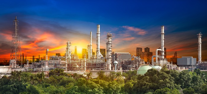Oil refinery shown with a multi colored sky.