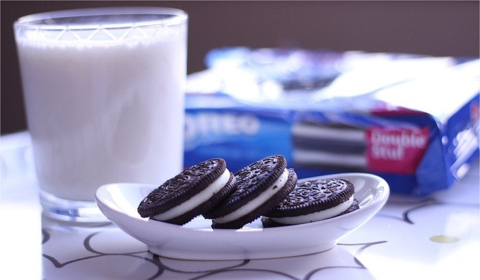 A plate of Oreos and a glass of milk.