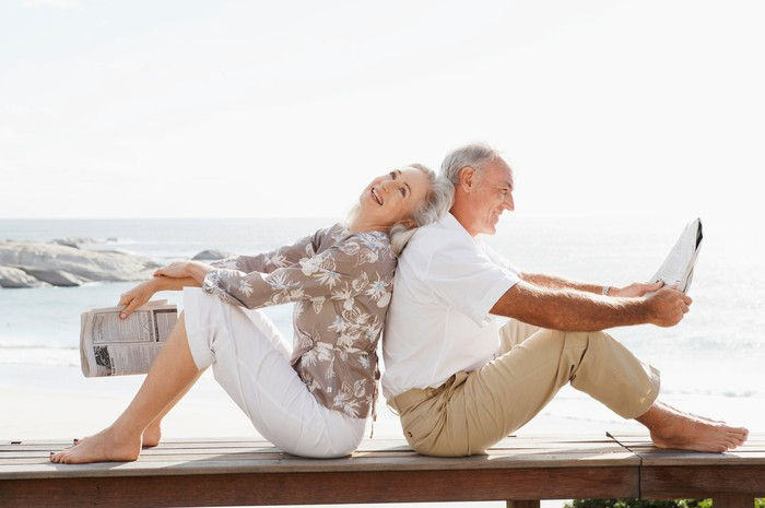 En elderly couple, sitting back to back on the beach, smiling, and holding newspapers.
