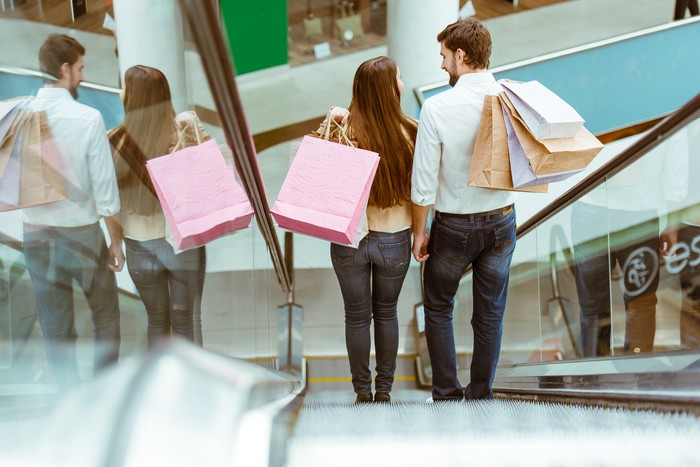 Couple going down an escalator with shopping bags.