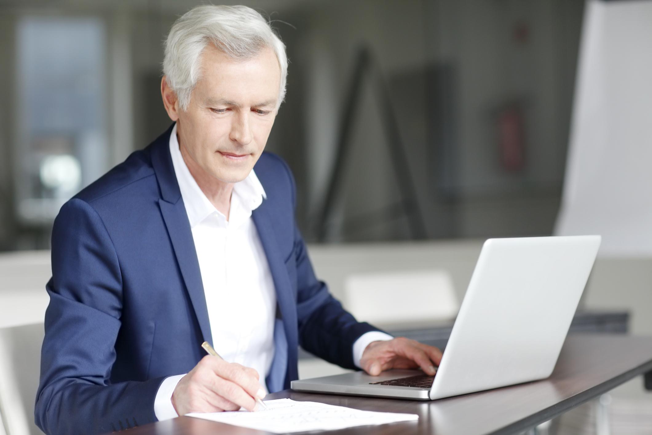 Older man working on a laptop