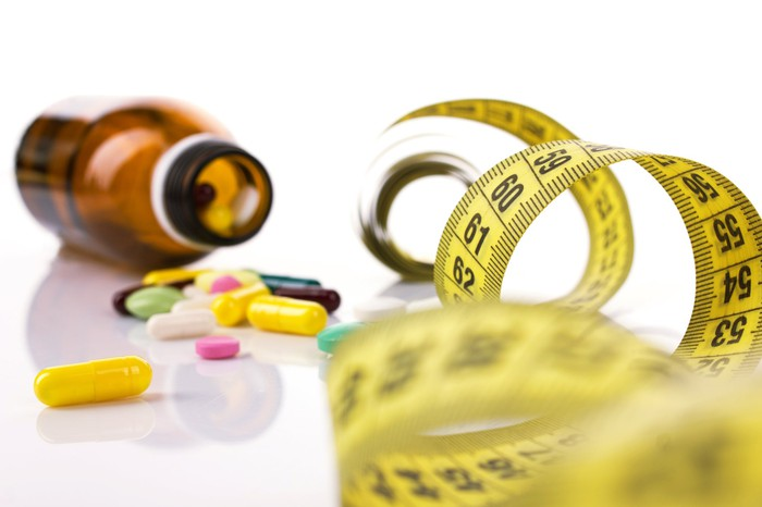 An open bottle is turned on its side, with colorful pills spilling out next to a tape measure.