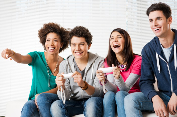 A group of friends huddled on a couch playing video games.