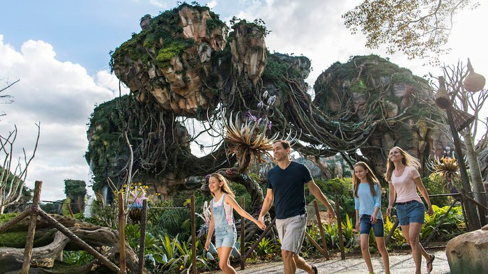 A family walking in front of a floating mountain at Pandora -- The World of Avatar.