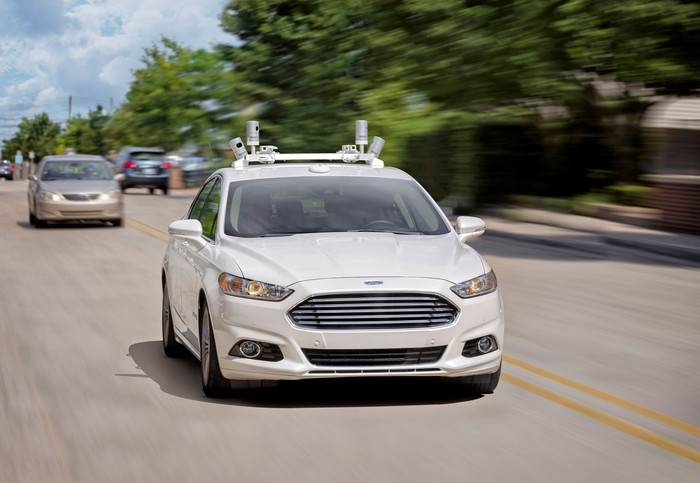 A white Ford Fusion sedan with self-driving sensor hardware on a suburban road