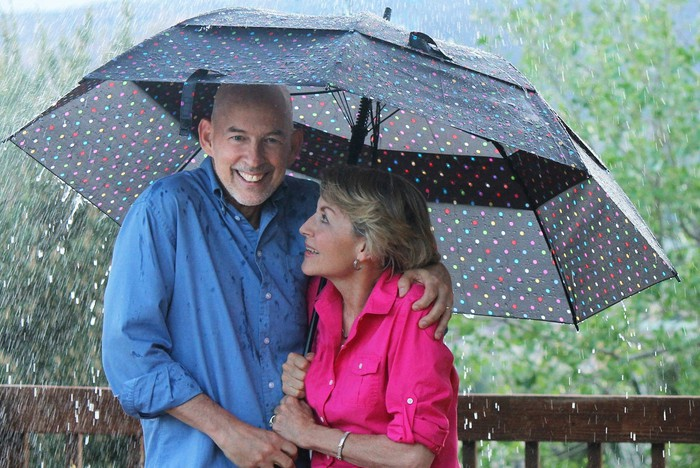 A senior couple smiling under an umbrella in the rain.