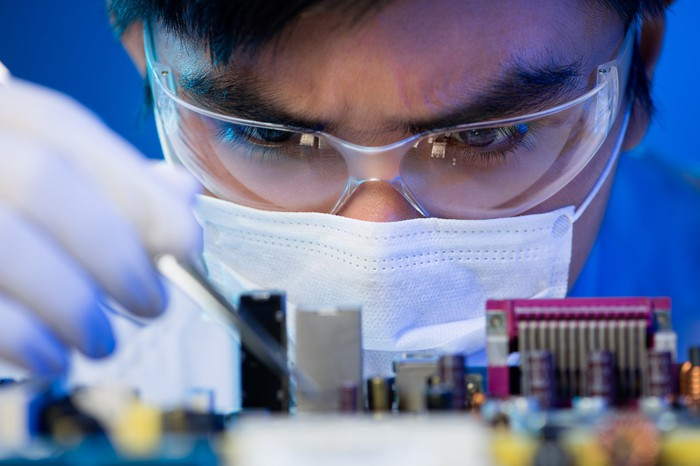 An engineer works on a circuit board.