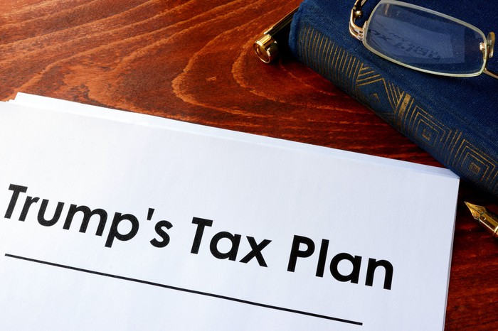 "The words ""Trump's Tax Plan"" appear on a stack of papers on a desk, next to a pair of reading glasses."