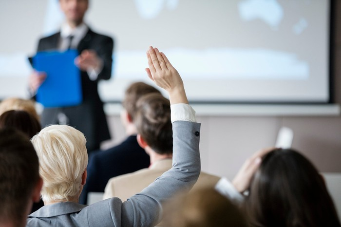 A woman raises her hand at a meeting.