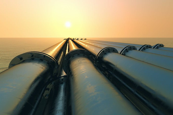 Pipelines over water at sunset.