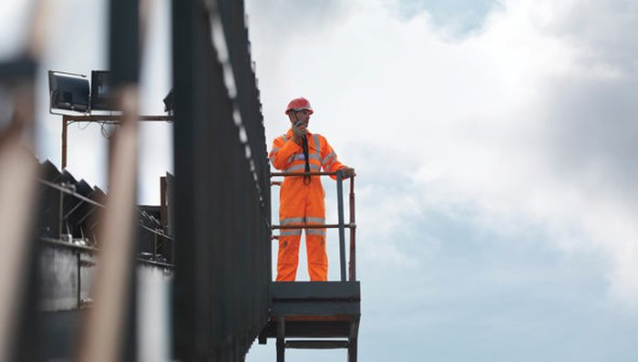 A worker in an orange jumpsuit standing on a catwalk talking into a mobile phone.