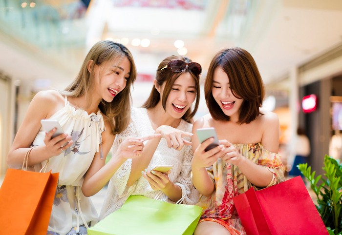 Three young Chinese women laughing, using their smartphones.