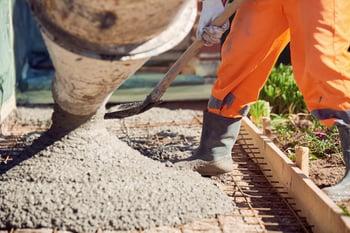 Worker spreading concrete.