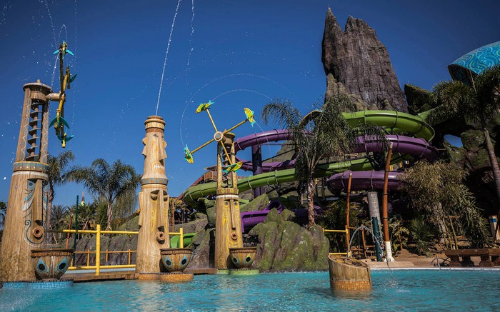 Water-shooting tiki statues in front of the volcano at Volcano Bay.
