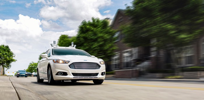 A white Ford Fusion sedan with autonomous-driving sensors visible, on a suburban road