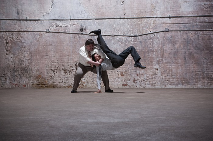 Two middle-aged men in business attire fighting in warehouse.