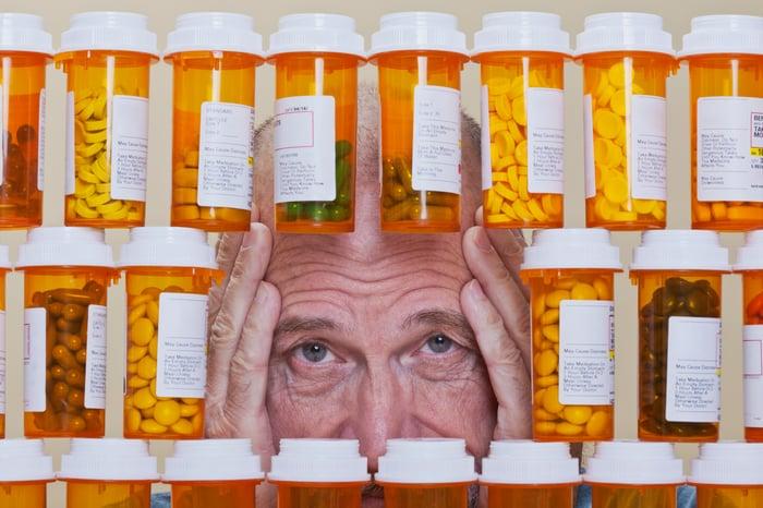 A man staring through a pile of prescription medicine bottles.
