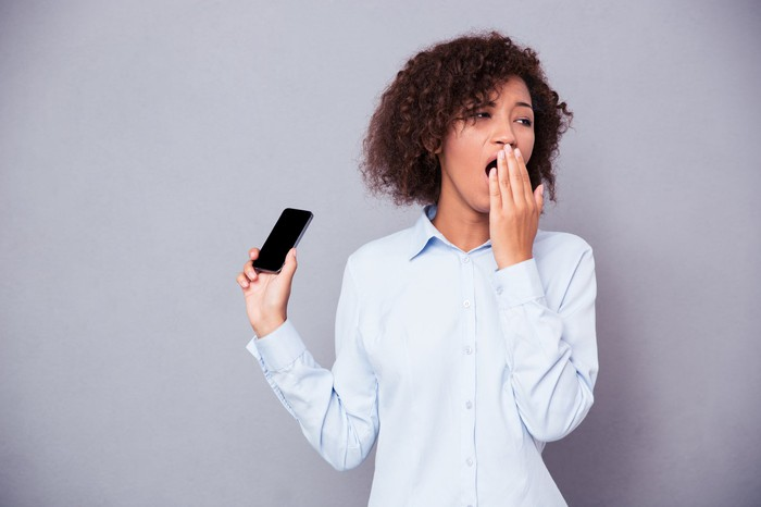 Woman holding a smartphone while yawning.