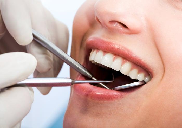 Smiling woman undergoing dental exam