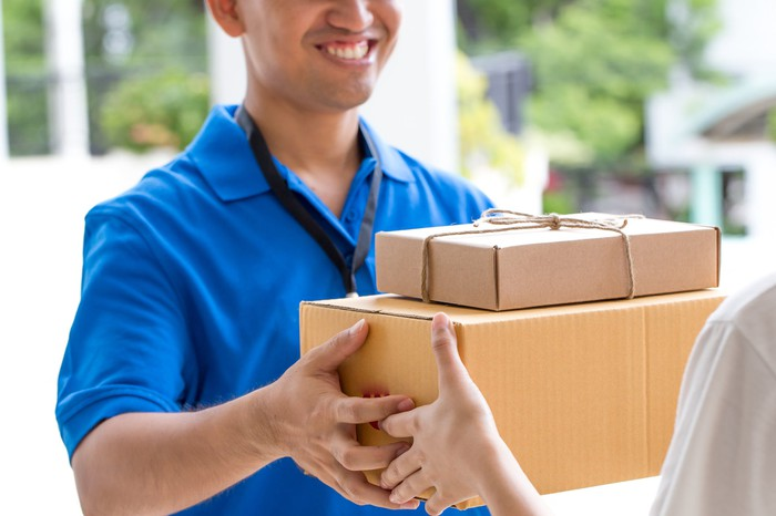 A person delivers a box of items to a customer's home.