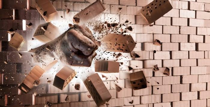Fist smashing through a brick wall.