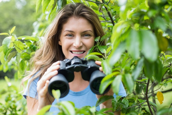 Woman behind some bushes, with binoculars and a big smile.