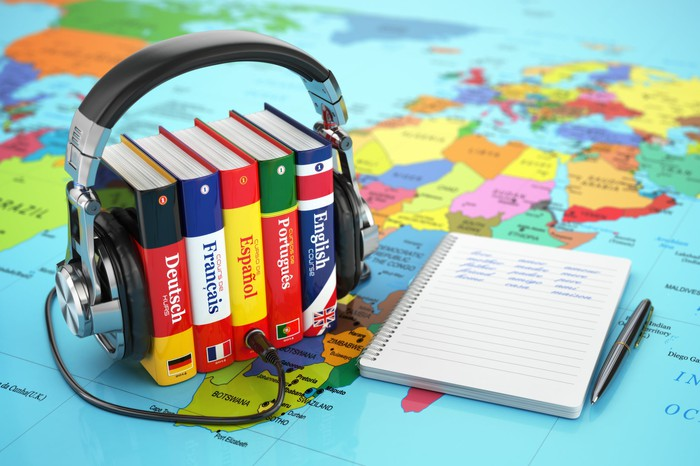 A pair of headphones are wrapped around a group of foreign-language dictionaries, sitting on a map and lying next to a pen and pad of paper.