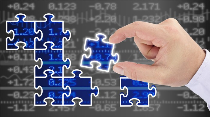 Hand putting pieces of a puzzle together revealing a blue glowing stock wall financial business success concept
