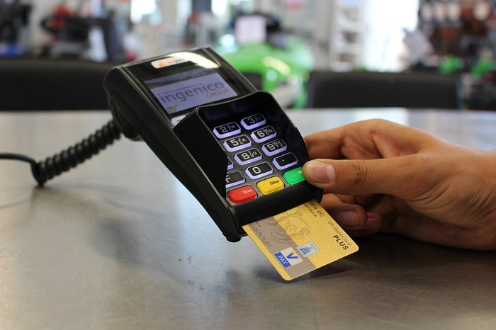 Merchant inserting EMV-chip credit card for payment.