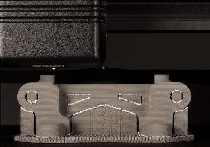Close-up of a Desktop Metal 3D printer printing a metal part.