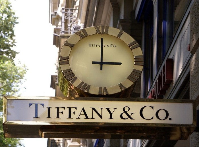 A sign and a clock at a Tiffany's store.