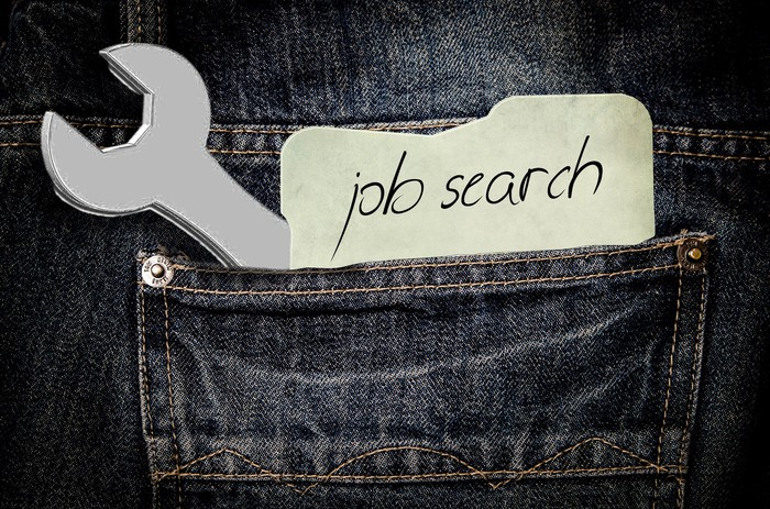 """A wrench and a note that says """"job search"""" are sticking out of the pocket of a pair of jeans."""