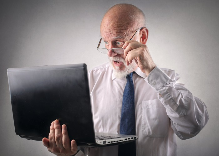 A man stares at a laptop cradled in his hand, looking over his glasses with surprise.